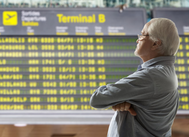Un senior dans un terminal d'aéroport.